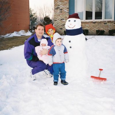 Joslin with her dad and brothers building a snowman